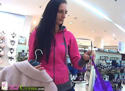 Slim brunette girl choosing her clothes in store
